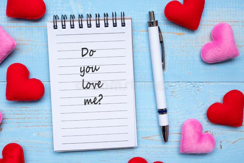 您是否爱我?在笔记本和笔的词与在蓝色木桌背景的红色和桃红色心形装饰 爱,婚姻 免版税图库摄影