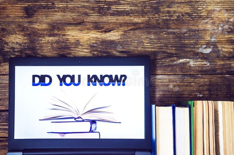 您是否知道?膝上型计算机和书在木背景 皇族释放例证