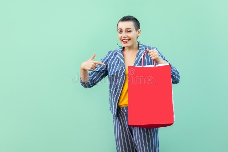 您是否要?画象满意美丽与镶边衣服身分的短发年轻女人,拿着购物的红色袋子和 库存图片