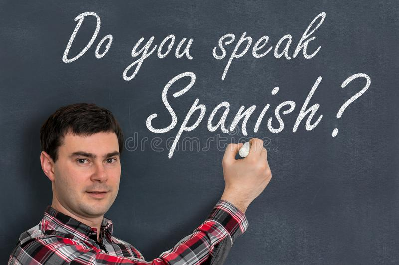 您是否讲西班牙语?有白垩文字的人在黑板 免版税库存照片