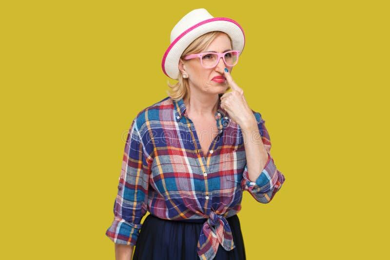 您是说谎者 恼怒的现代时髦的成熟妇女画象便装样式的与帽子,站立的镜片看和接触 免版税库存图片