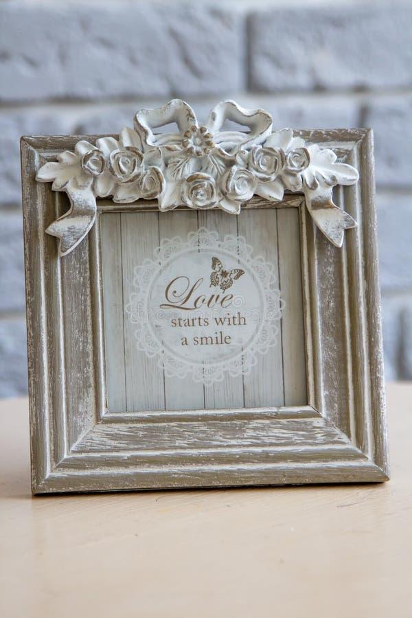 您的图片的老破旧的方形的框架,照片,在棕色光滑的桌上的图象有灰色砖墙背景 免版税库存照片