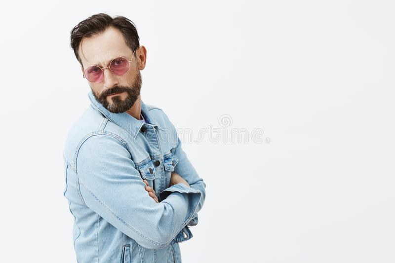 您谈话与星 有胡子的严肃确信的欧洲人在时髦太阳镜和牛仔布夹克,举行 图库摄影