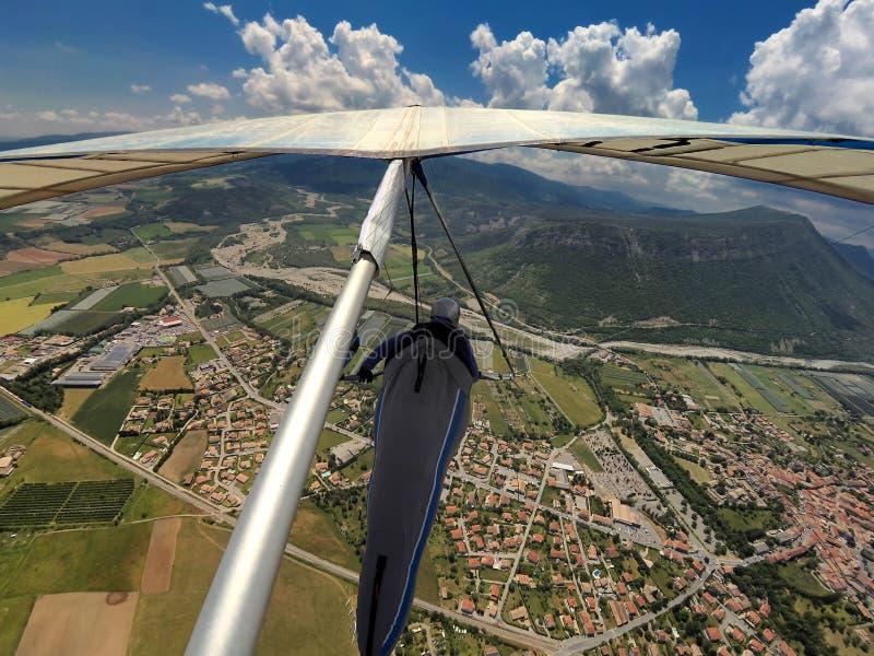 悬挂式滑翔机飞行员飞行高在高山地形在Provance, Fr 库存图片