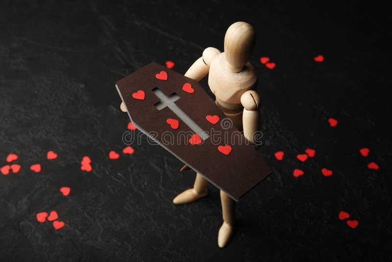 悲伤和挽歌 一个木人在他的手上拿着一个棺材有哀痛红心的  库存照片