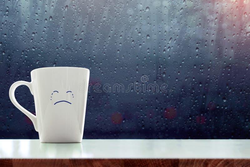 悲伤有哭泣的面孔动画片的咖啡杯在屋子里面,蓝色 库存照片