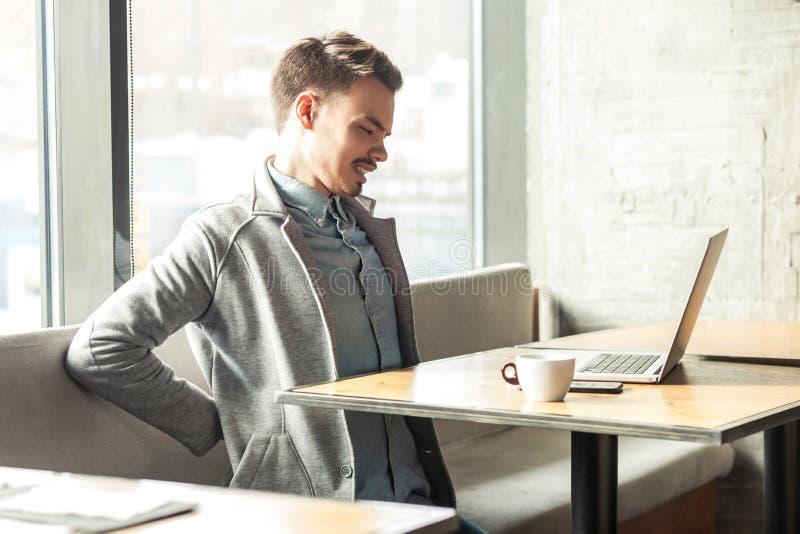 悲伤痛苦的疲乏的有胡子的年轻自由职业者画象灰色燃烧物的在咖啡馆单独坐并且举行他的与 免版税库存图片