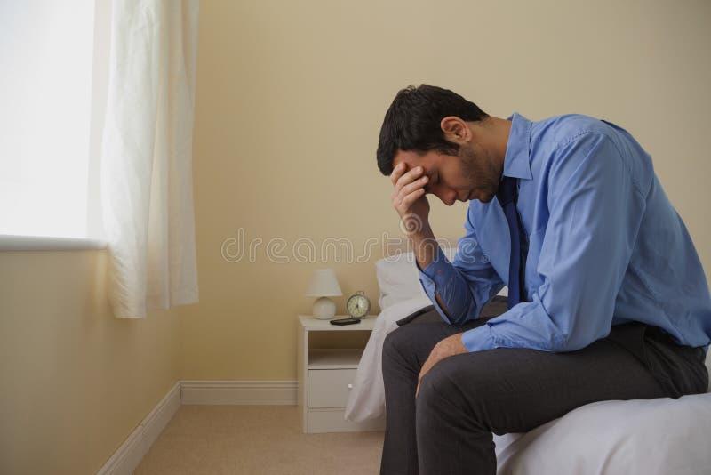 悲哀的人坐的头在他的床上的手上 免版税库存照片