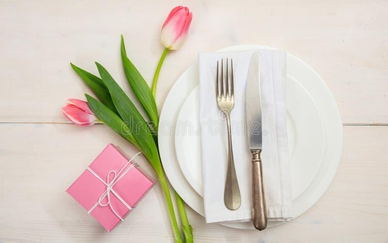 情人节与桃红色郁金香和一件礼物的桌设置在白色木背景 顶视图 库存图片
