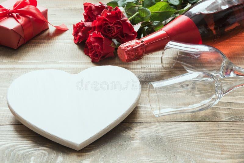 情人节与花束红色玫瑰的贺卡开花,一个瓶香槟,心脏作为空白和在木桌上的礼物盒 Co 库存图片