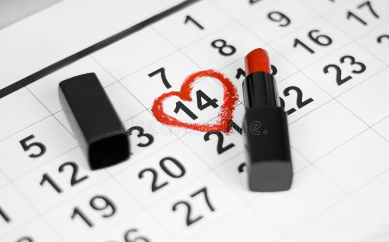 情人节和假日概念 日历板料与2月14日日期由与红色口红的红心形状表示 关闭 免版税库存照片