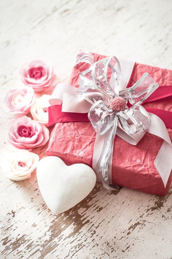 情人节和母亲节概念、红色礼物盒有弓的和玫瑰在轻的木背景 免版税图库摄影