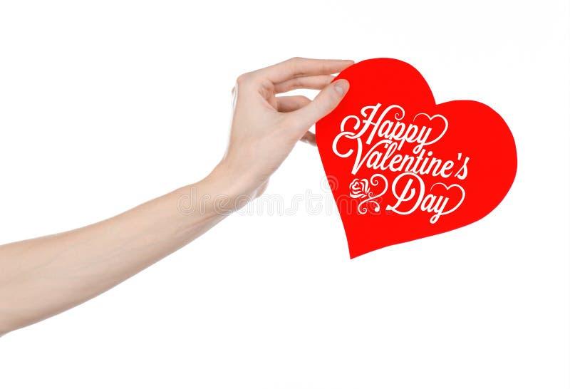 情人节和爱题材:手拿着一张贺卡以红色心脏的形式与词愉快的情人节 免版税库存图片