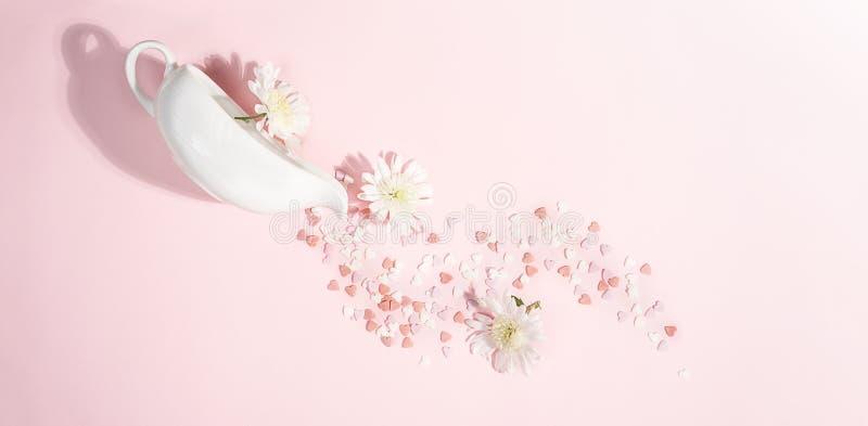 情人节在粉红彩笔背景的装饰布局与花、心脏和白色厨房调味汁瓶 婚姻最小的爱 免版税库存图片