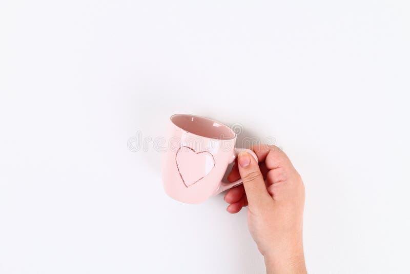 情人节布局 有心脏的桃红色杯子在手中在白色背景 St情人节,天爱,2月14日概念 复制 库存图片