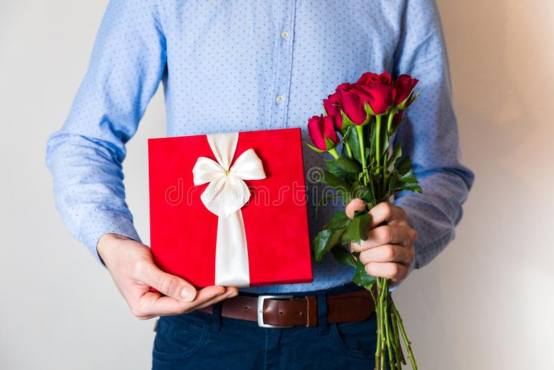 情人节惊奇,爱,拿着浪漫礼物和英国兰开斯特家族族徽花束的帅哥 免版税库存图片