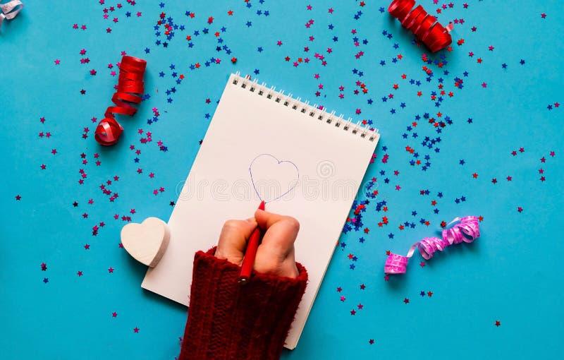 情人节愿望 在蓝色背景的笔记本与闪闪发光 库存照片