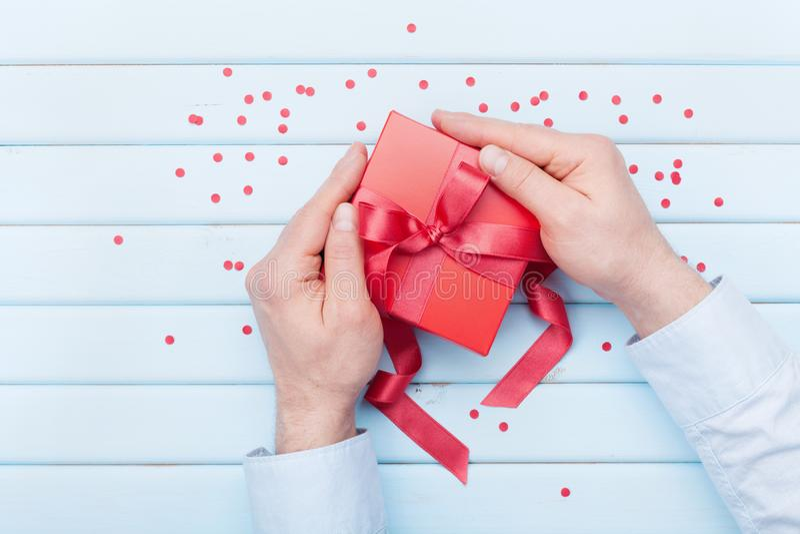 情人节或圣诞节贺卡 人在手上拿着一个礼物盒 顶视图 平的位置样式 免版税库存图片