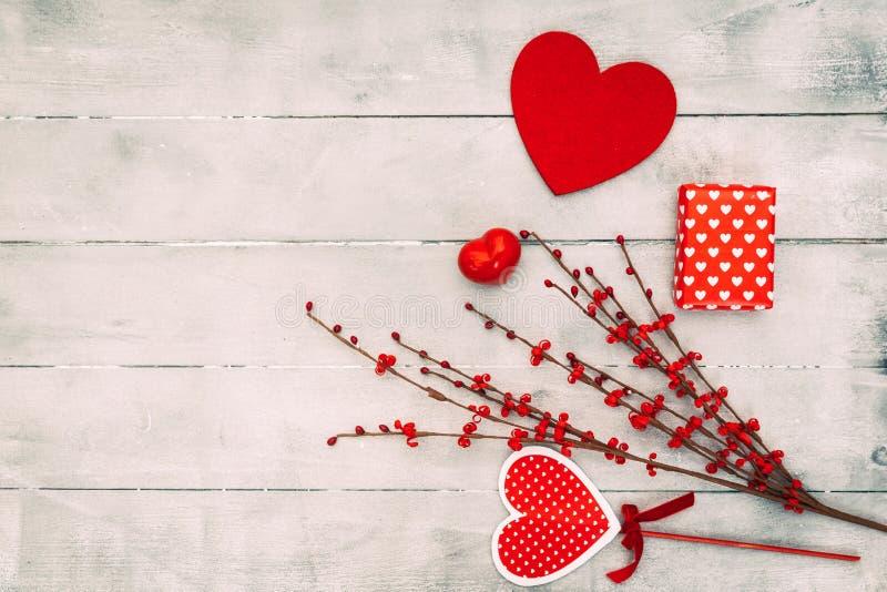 情人节构成 红色心脏,礼物盒,在木背景 爱或浪漫概念 平的位置 免版税库存图片