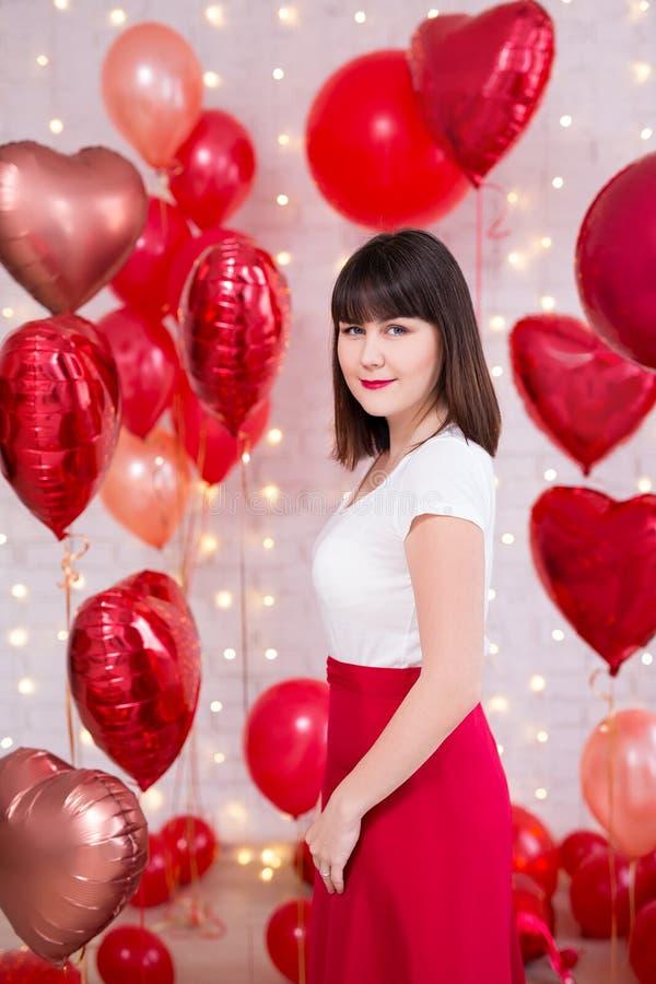 情人节概念-摆在与红色气球的愉快的美女 库存照片