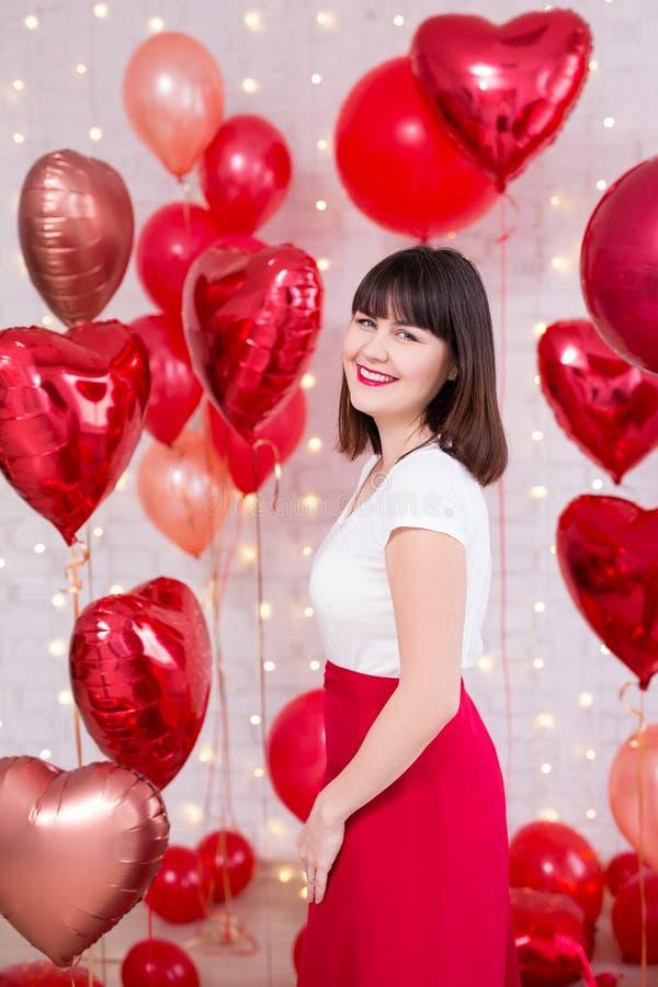 情人节概念-摆在与红色气球的笑的美女 图库摄影