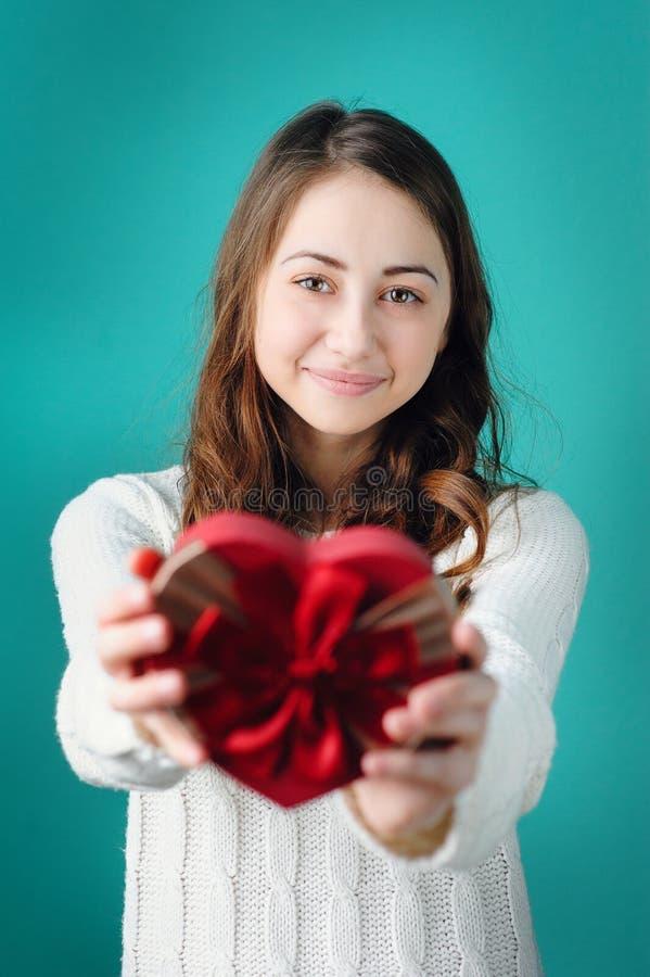 情人节概念 有礼物的美丽的年轻微笑的妇女以心脏的形式 库存图片