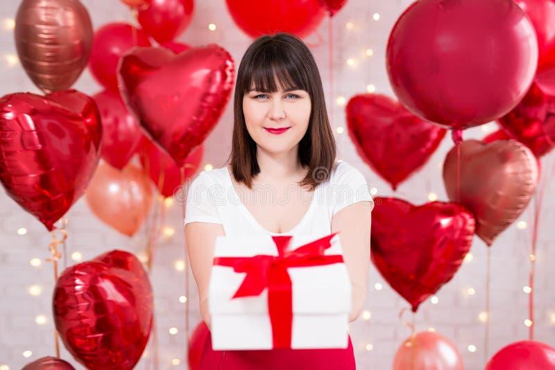 情人节概念-有礼物盒和红色气球的愉快的美女 免版税库存照片