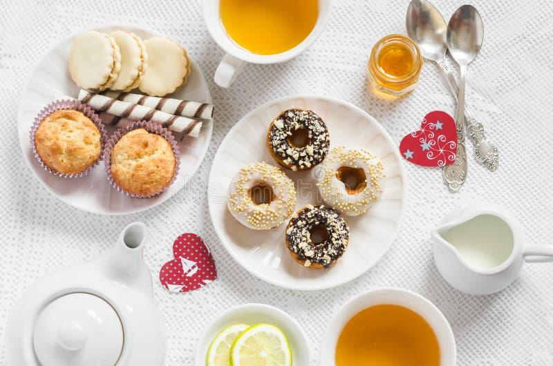 情人节浪漫早餐柠檬绿茶和甜点-香蕉松饼、曲奇饼用焦糖和坚果,油炸圈饼l 库存照片
