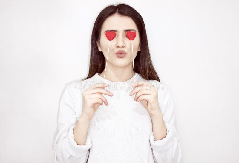情人节爱美好的概念 拿着在她的眼睛的愉快的女孩两心脏 库存照片