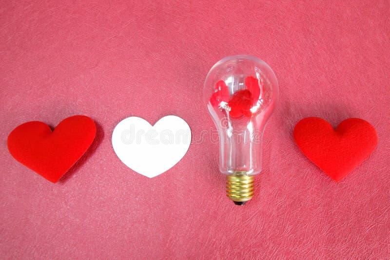 情人节白色和红心与电灯泡在桃红色背景 库存图片