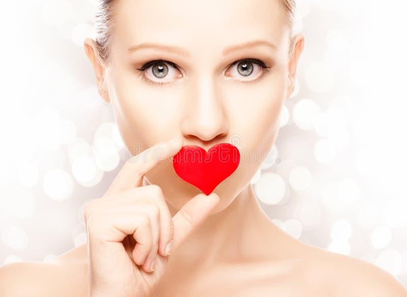 情人节的概念。有红色心脏的女孩在嘴唇 免版税图库摄影