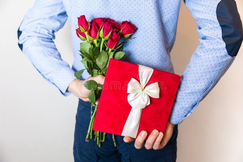 情人节礼物惊奇,人掩藏的礼物和拿着红色玫瑰色花束 库存图片