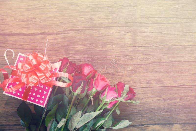情人节礼物盒花爱概念桃红色有丝带弓英国兰开斯特家族族徽的礼物盒在木桌上开花 免版税库存图片