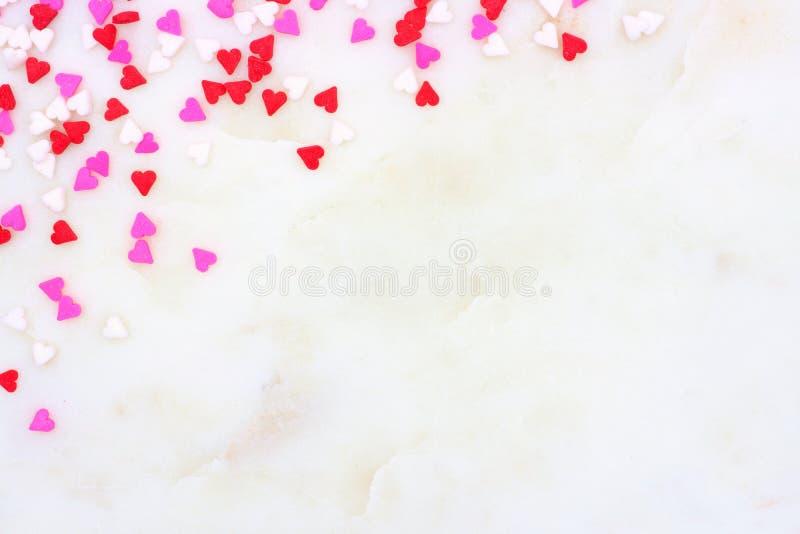 情人节糖果心脏洒在白色织地不很细背景的壁角边界 库存图片