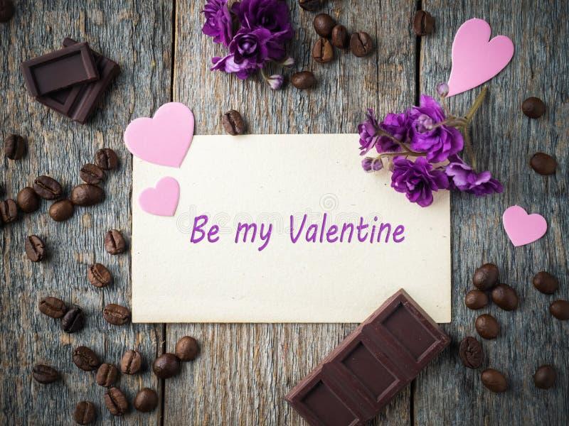 情人节纸心脏、紫罗兰、咖啡和巧克力的装饰在老纸和木头背景 免版税库存图片