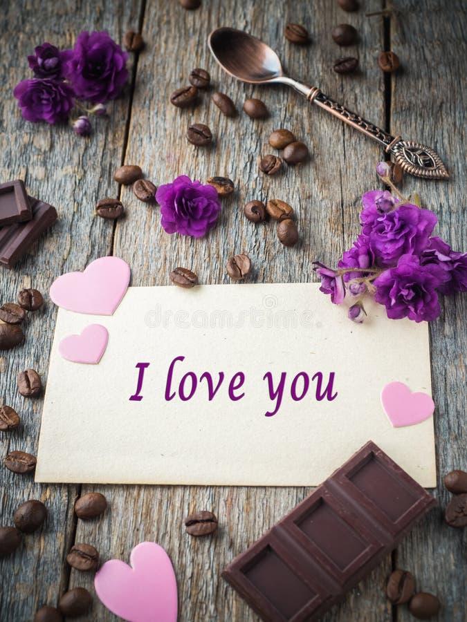 情人节纸心脏、紫罗兰、咖啡和巧克力的装饰在老纸和木头背景 免版税图库摄影