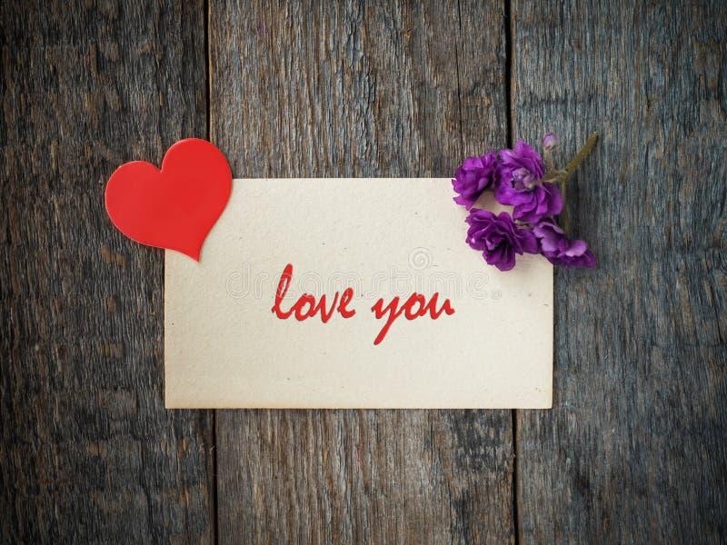 情人节纸心脏的装饰,在老纸和木头背景的紫罗兰题字爱您 库存图片