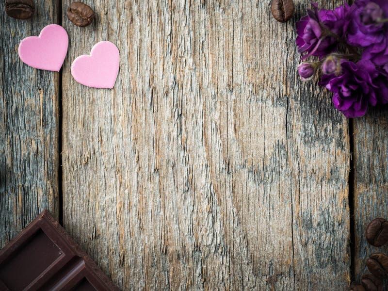 情人节纸心脏的装饰,紫罗兰和巧克力咖啡在土气木背景 库存照片