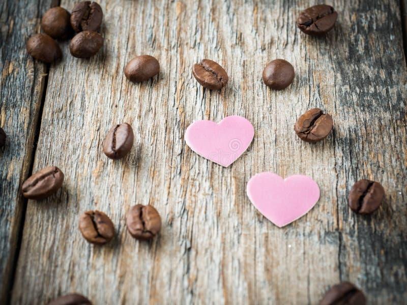 情人节纸心脏的装饰,紫罗兰和巧克力咖啡在土气木背景 免版税库存图片