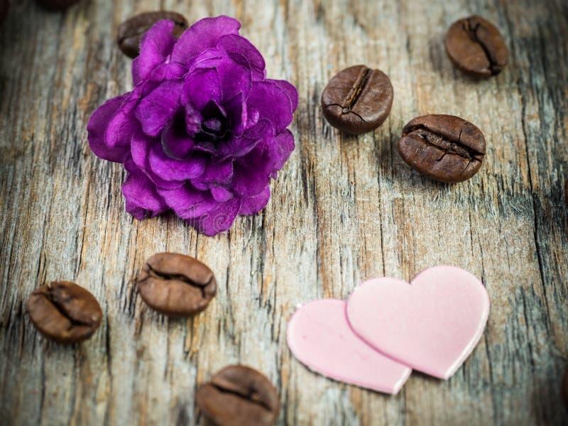 情人节纸心脏的装饰,紫罗兰和巧克力咖啡在土气木背景 免版税库存照片