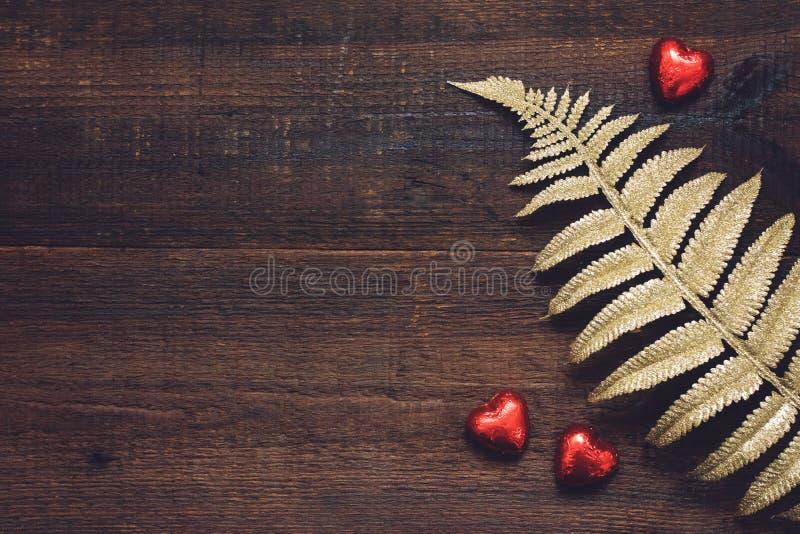 情人节背景、大模型用红心形状巧克力糖和金黄叶子在木背景 情人节, 免版税库存图片