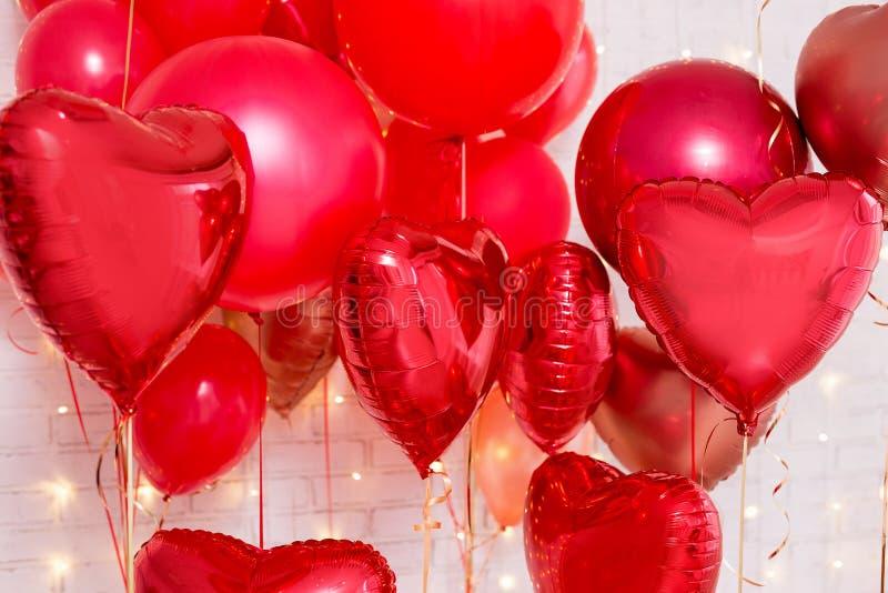 情人节背景-在砖墙的红色心形的气球 库存图片