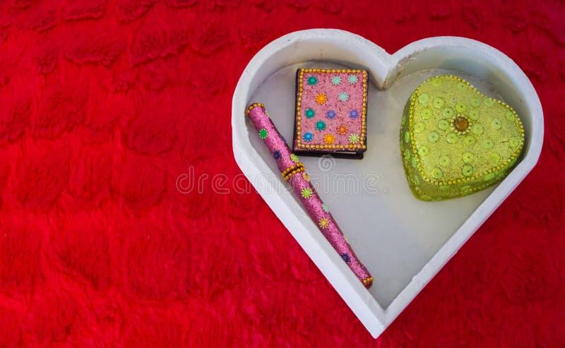 情人节装饰背景、一个白色心形的箱子有笔的,放置在一个红色枕头的笔记本和心形的箱子 库存照片