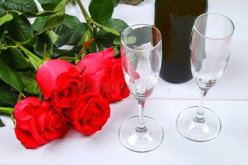 情人节贺卡、红色玫瑰花、酒杯和礼物盒在木桌上 顶视图 免版税图库摄影