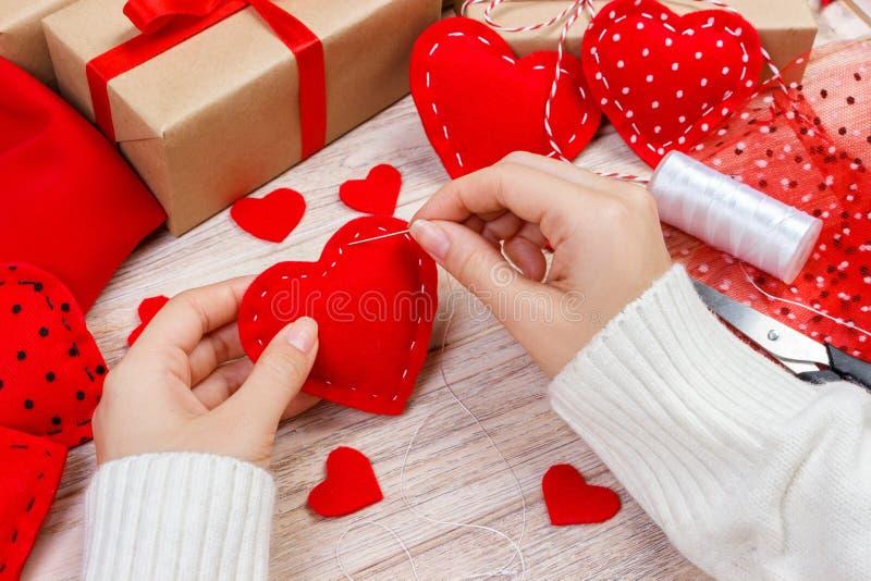 情人节题材 准备的手工制造装饰工作场所 女性手顶视图缝合毛毡心脏 被包装的礼物,嘘工具 免版税库存照片