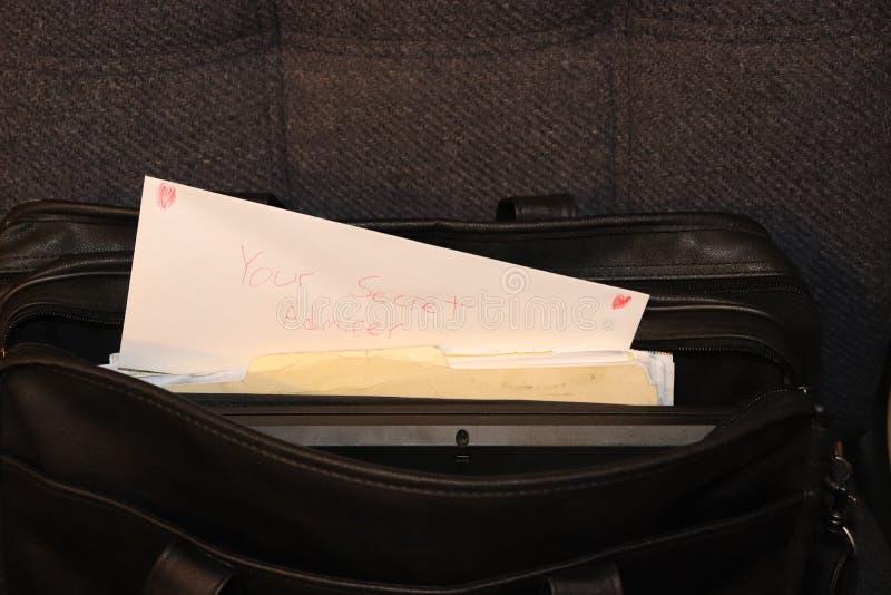 情人节黏附在公文包外面的爱信封说`您的秘密钦佩者` 库存照片
