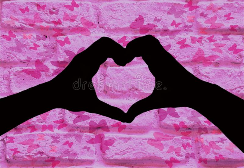 情人节,一起做心形的两只手剪影在有蝴蝶的一个桃红色砖墙 图库摄影
