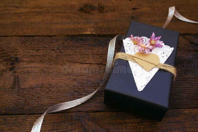 情人节,生日工艺有装饰黑色纸当前箱子的礼物盒有心脏的,鞋带餐巾,在木背景的黄麻绳索 免版税库存图片