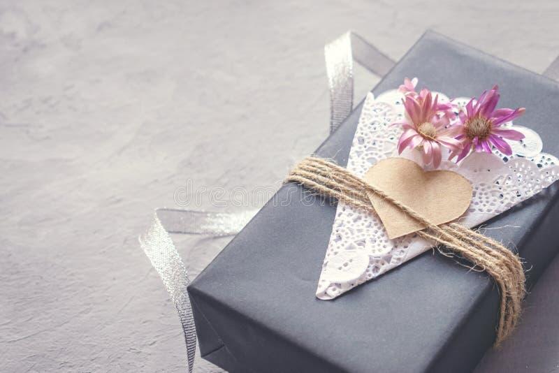 情人节,生日工艺有装饰黑色纸当前箱子的礼物盒有心脏的,鞋带餐巾,在灰色水泥的黄麻绳索 免版税库存照片