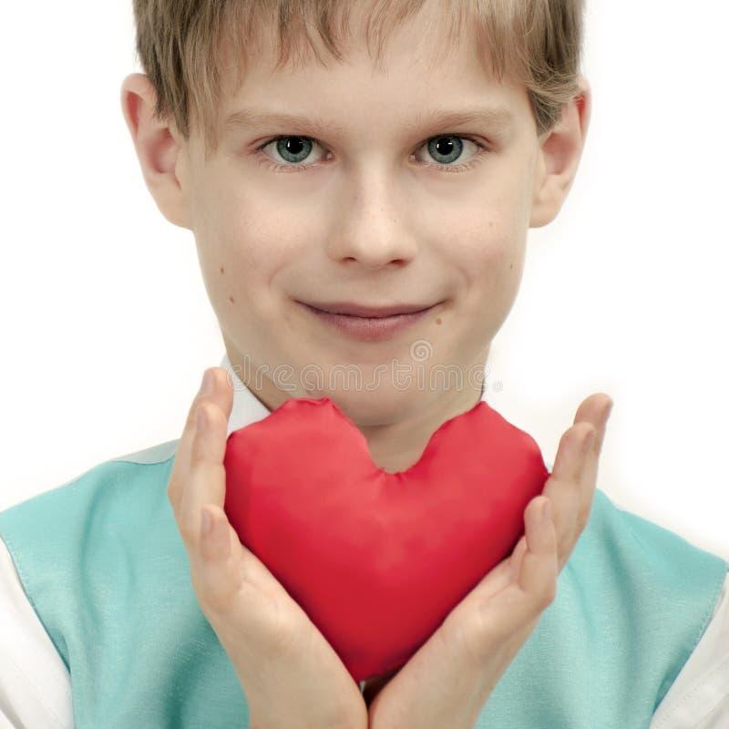 情人节-有红色心脏的逗人喜爱的孩子在手上。 免版税库存照片
